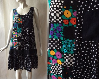 1980's / 1990's drop waist jumper dress, flower and polka dot print in black, bright multicolor, and white, by Jeannette, about a medium