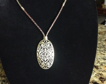 Monet vintage large filagree pendant on a leather lariat attached to a multi-link chain with lobster clasp.
