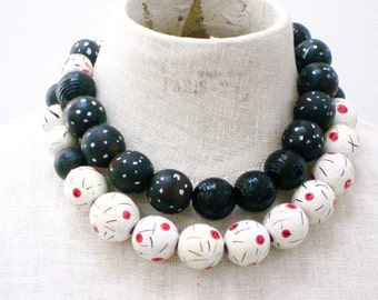 Short double strand necklace.  Wood beads are hand painted.  Colors are black and white and red.