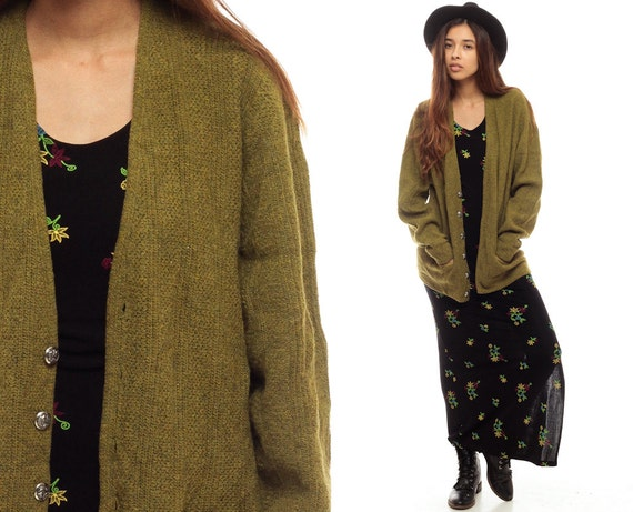Olive green and multicolor vintage Chanel mohair-blend open bouclé knit cardigan with crew neck, long sleeves and gunmetal-tone interlocking CC button closure at front. From the Fall Collection.