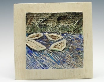 Hand sculpted ceramic tile of boats resting at low tide in kinvarra port in Ireland. Relief tile boats at low time.