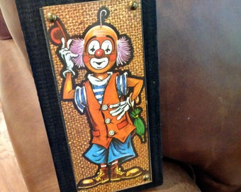Vintage art work of clown on wood plaque with rustic chain