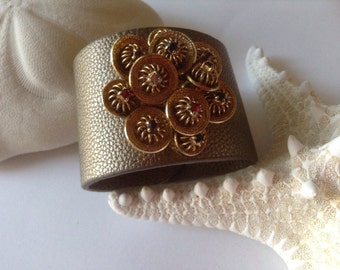 Wide antique gold finish cuff bracelet featuring goldtone brooch with multi color stone accents.