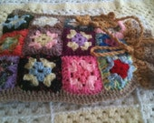 Hand crocheted 24 piece granny square hot water bottle cover with gathered top for easy access water fill, cord finished off with flower