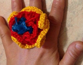Cotton crocheted ring with heart in recycle plastic.