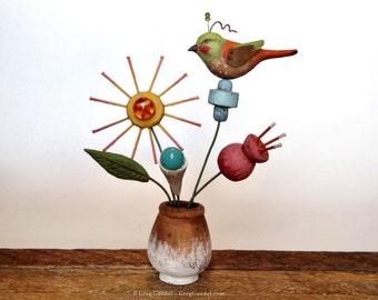 Folk art bird on flowers sculpture