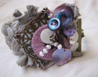 Cuff bracelet made of a grey fabric strip, decorated with a filagree, vintage buttons, charms made out of shells or covered cotton, upcycle