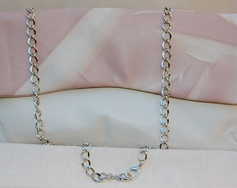 Two tone convertible clutch in butter-soft Italian lambskin, with silver chain strap and silver snap closure.  Fully lined with two pockets.