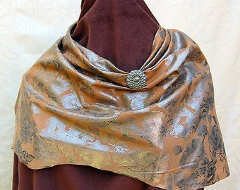 Brown leather asymmetrical scarf with floral design of silver foil, and antique matching silver button embellishment.