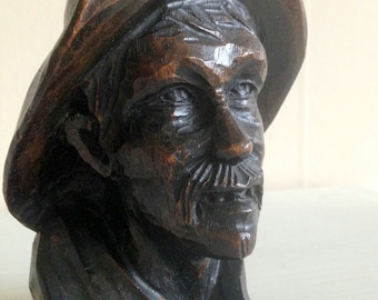 A hand-carved wooden head of dark trees