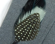 Olive feather boutonniere accented with spotted guinea feather and green rhinestones