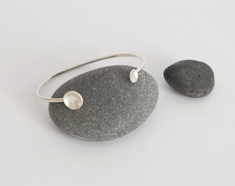 Modern and organic silver cuff bracelet, with two domed circles