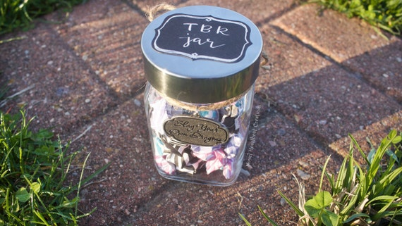 "Small bookish ""TBR Jar"" with origami star book titles, ""Slay your own dragons"" charm"