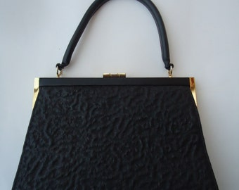 Vintage 60s leather handbag.  Trapeze shape. Black, bumpy texture.  Leather purse, metal frame. Very good condition.