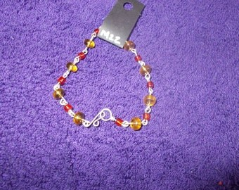 7 inch bracelet, red and amber stones, silver plate clasp and chain.   Stock #M-22