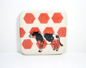 porcelain art tile / trivet with a holstein cow print on red-orange hexagons. made to order / pick your colour
