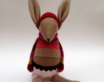 Oatmeal Woollen Rabbit - Handmade plush sculpture wearing stripey woollen pullover and felt shorts.