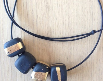 Glam Black Necklace. Black beaded necklace with Gold Leaf on black or gold coloured silk cord.