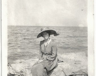 Old Photo Woman at the Beach sitting on Rock wearing Long Dress and Hat 1910s Photograph snapshot vintage