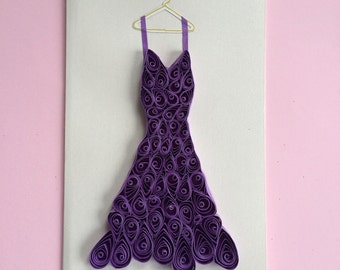 Card with purple, quilled dress on hanger.