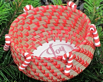 "Cute and colorful hand-stitched and coiled pine needle basket with ceramic candy cane beads and a ""Joy"" ceramic base entitled ""Sweet Joy""."