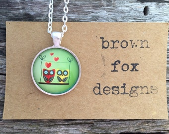 Perched owls circle silver pendant necklace