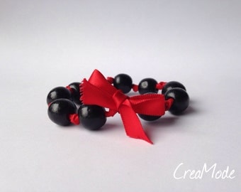 Bracelet adorned with round beads mounted on a satin ribbon.