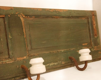 Vintage architectural salvage coat rack, electric insulator on old shabby painted board,  wooden coat rack