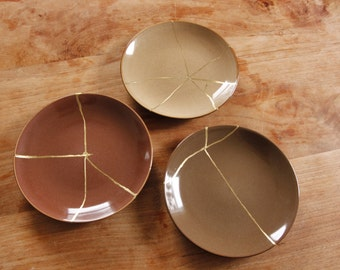 Light brown earth colored plate repaired with Kintsugi