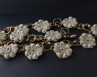 Photo/note wall hanging. Braided tubular elastic webbing (red, bronze and gold), gold-coloured chain, crocheted gold flowers, magnets (#76)