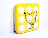 tile with a chicken/hen on yellow with white hexagons, ready to go.