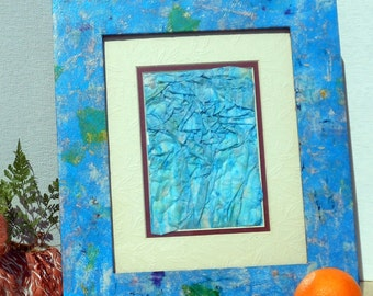 Tissue collage frame for picture wide blue wood border with tie dyed tissue paper bits collage in pastel yellow white pink green vegan