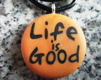 Life Is Good hand carved on a polymer clay orange pearl color background. Pendant comes with a FREE necklace