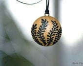 A wooden pendant with a leaf design painted by hand with oil paints. Colors are black and wood-color, size 3 cm, natural look