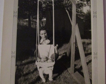 Vintage B&W photo of mother in glasses and baby in swing, mid-century
