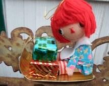 Vintage 1970s Japan Raggedy Ann Styrofoam Head Christmas Ornament Hanging Doll On Sled With Presents Bobbs-Merrill Co.
