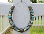 Beaded decorative horseshoe with white, turquoise, silver and ivory colored beads and metal star button for horselovers or to wish good luck