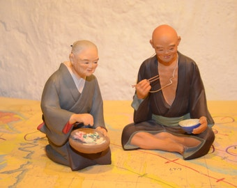 Vintage Pair Hakata Urasaki Doll of Elderly Couple Eating Fish and Rice - Toothless Old Man With Rice Bowl, Old Woman with Sashimi in Basket