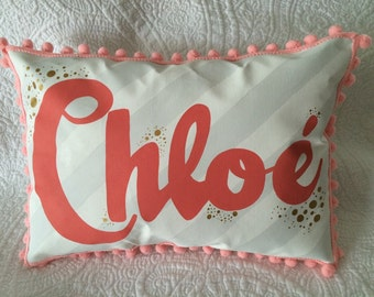 Baby pillow in light gray stripes with bright coral personalized name.