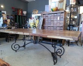 French iron dining table base with salvaged wood from vintage boxcars