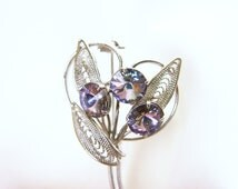 Silver wire brooch with lavender rhinestone flowers. Coiled silver wire and soft purple rhinestones