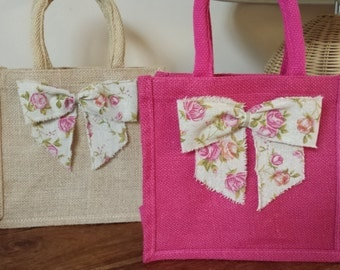 Beautiful hand finished jute lunch or gift bag with padded handles and a pretty hessian ribbon bow. Pink or Natural.