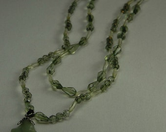 GNGN_010 Green on green with a variety of shapes / sizes of beads create this double strand 19 and 17 inch with jade-like pendant necklace.