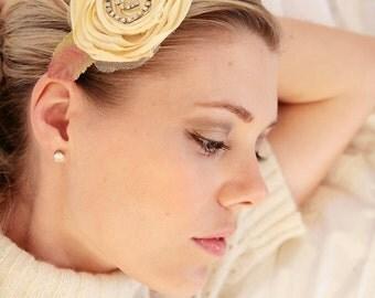 Pale yellow/sage green flower headband with fabric leaf and rhinestone swirl accent on satin headband.