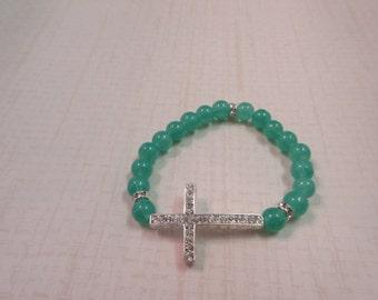 Green glass beaded bracelet with silver sideway cross.