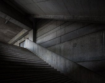 Chiaroscuro photography of stairs in a concrete building in Paris