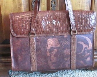 Handpainted skulls and wings decorate this leather tote