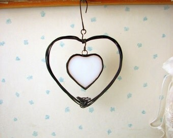Stained glass heart hanging inside a metal wire heart