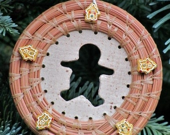 Cute hand-stitched and coiled pine needle Christmas ornament with gingerbread house beads and gingerbread boy cutout ceramic center.