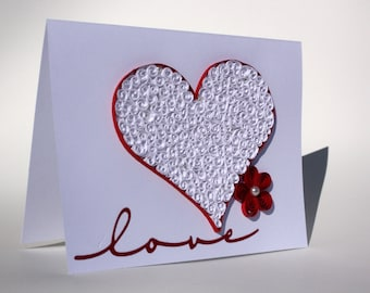 """Quilled """"Love"""" blank greeting card. Elegant pearls layed in a lacy heart with red accents."""